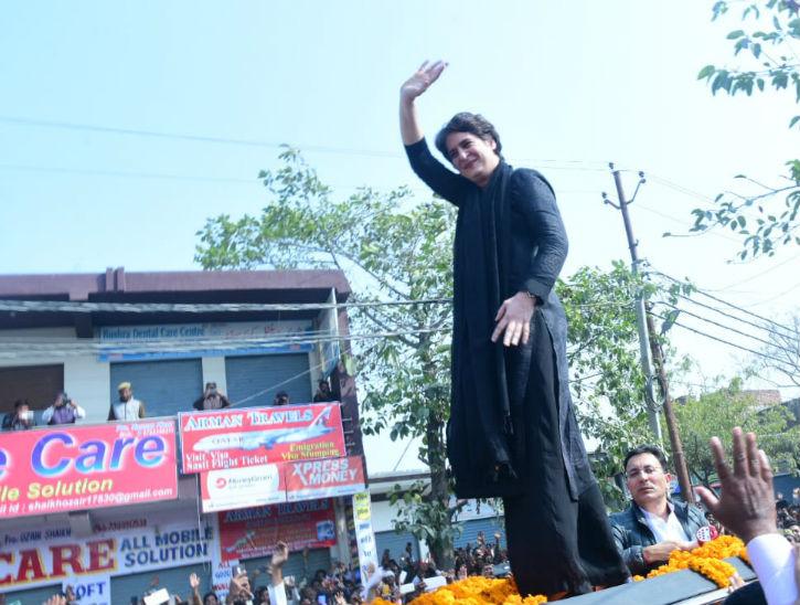 गाड़ी के उपर चढ़कर लोगों का अभिवादन करतीं प्रियंका गांधी।