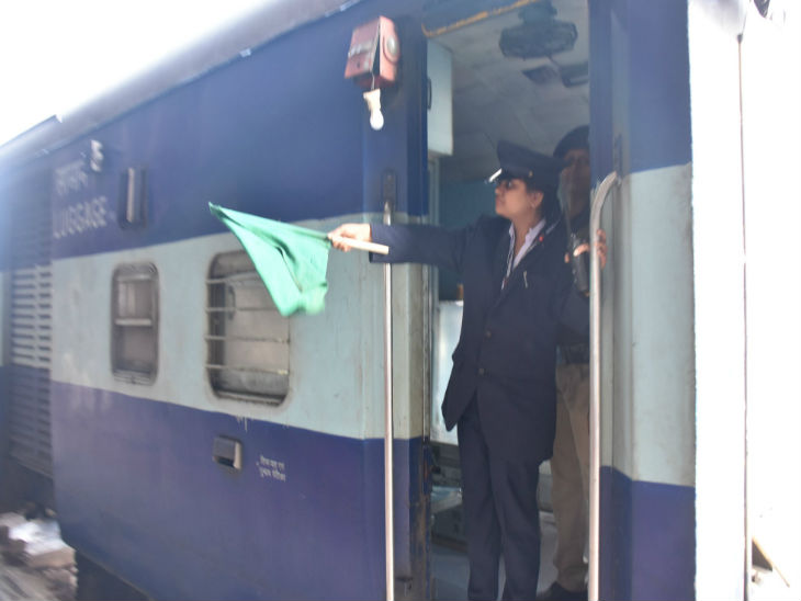 ट्रेन को हरी झंडी दिखाती महिला गार्ड। - Dainik Bhaskar