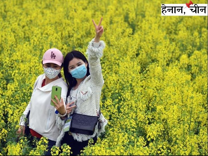 चीन के हेनान प्रांत में बसंत की बहार में कोरोना के डर के बावजूद सेल्फी ले रहीं लड़कियां। चीन ने वुहान और हुबेई प्रांत में कोरोना संक्रमण को काबू करने की घोषणा की है।