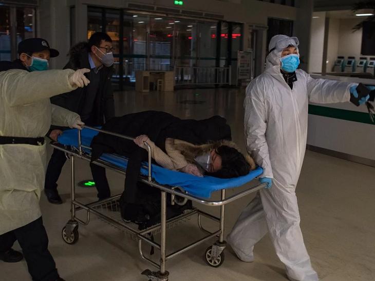 वुहान मेटरनल एंड चाइल्ड हेल्थ हॉस्पिटल में वॉलेंटियर एक गर्भवती महिला को कोरोनावायरस टेस्ट के लिए ले जाते हुए। - फाइल