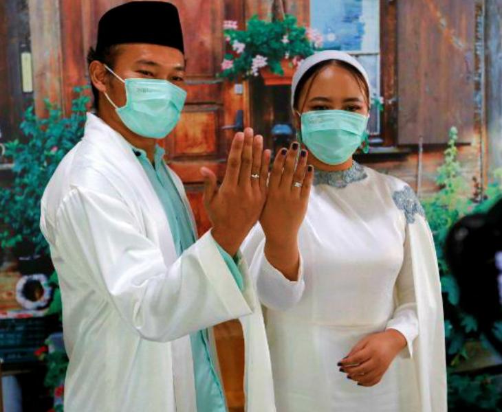 कोरोना के कहर के बीच कुछ देशों में शादियां भी हो रही हैं। तस्वीर इंडोनेशिया की राजधानी जकार्ता की है। शुक्रवार को यहां शादी के बाद कपल। दोनों ने फोटो सेशन के दौरान मास्क लगाए थे।