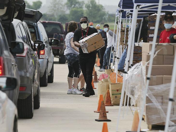 अमेरिका के ट्रेडर्स विलेज में सेंट एंटोनियो फूड बैंक से मिली राहत सामग्री ले जाता कर्मचारी।