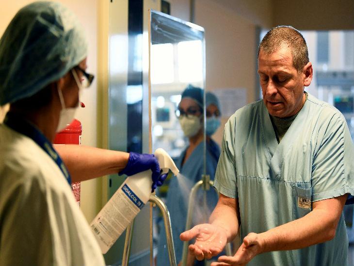 इटली के वेरेस स्थित एक अस्पताल के आईसीयू में जाने से पहले हाथ सैनिटाइज करता स्वास्थ्यकर्मी।