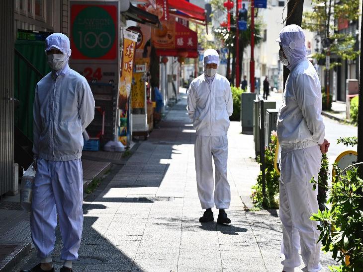 जापान के योकोहामा शहर में प्रोटेक्टिव गियर्स और मास्क पहनकर ग्राहकों का इंतजार करते रेस्टोरेंट के कर्मचारी।