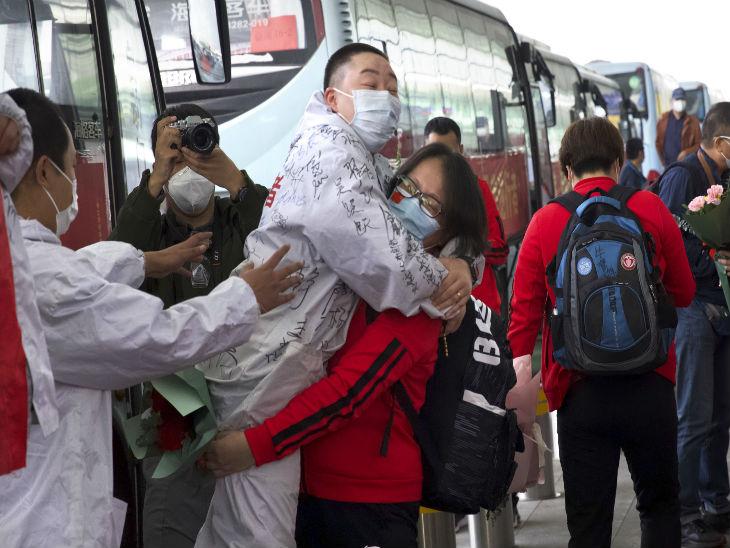 वुहान के इंटरनेशनल एयरपोर्ट पर अपने एक साथी को गोद में उठाकर ले जाती स्वास्थ्यकर्मी।
