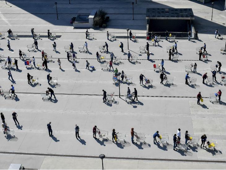 इटली: दुनियाभर में रविवार को ईस्टर मनाया जा रहा है। शनिवार को सुपरमार्केट के बाहर सोशल डिस्टेंसिंग का पालन करते हुए लाइन में लगे लोग।