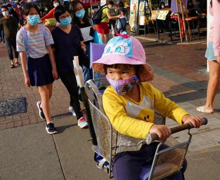 हॉन्गकॉन्ग में शनिवार को एक फेस मास्क लगाए साईकिल पर बैठा बच्चा। प्रशासन ने ईस्टर के एक दिन पहले यहां कुछ शर्तों के साथ लॉकडाउन में राहत दी थी।