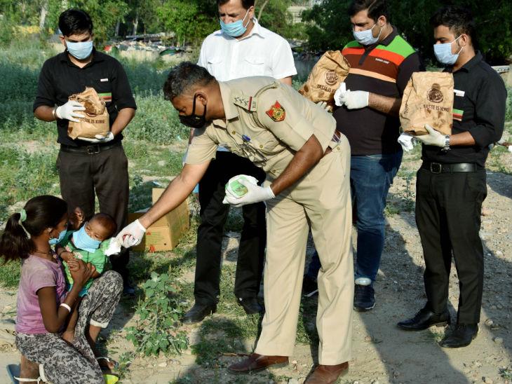 दिल्ली में सड़क किनारे बैठी बच्ची को पुलिस के जवान बर्गर देते हुए। लॉकडाउन की वजह से मजदूर बेरोजगार हो गए हैं और उनके लिए पेट पालना चुनौती बन गया है।