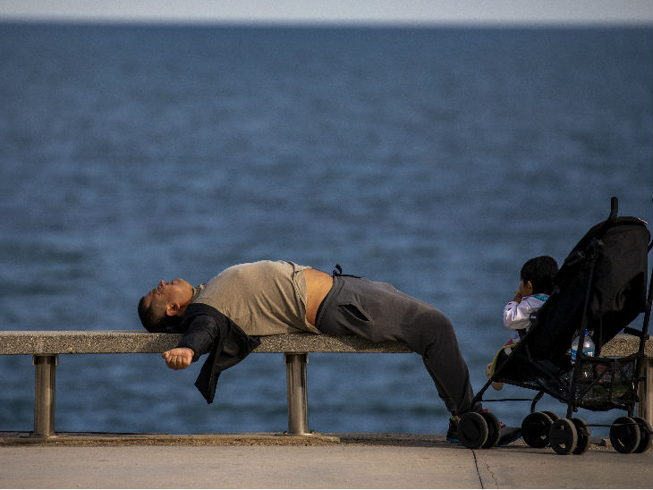 स्पेन के बार्सिलोना में भूमध्य सागर के सामने एक बेंच पर लेटा युवक। यहां अब तक 23 हजार से ज्यादा लगों की मौत हो चुकी है।