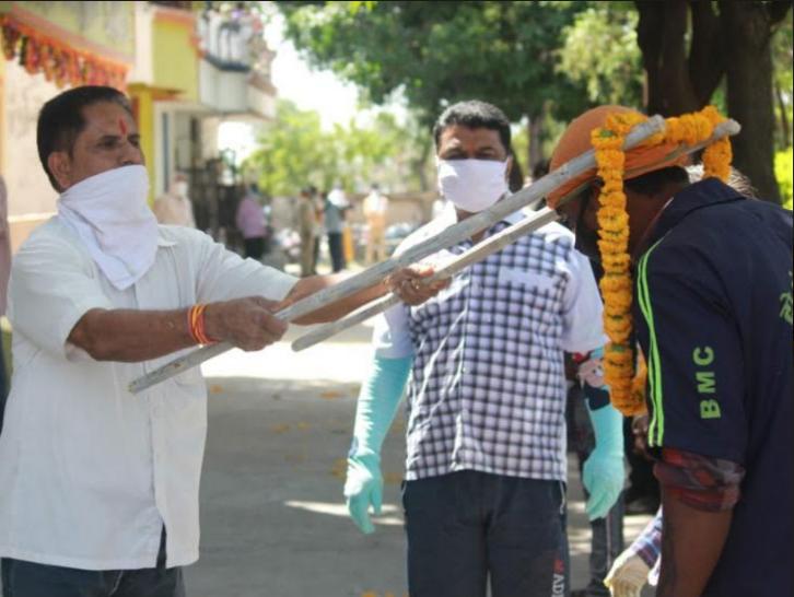 सम्मान में सोशल डिस्टेंस: भोपाल में सफाईकर्मियों का सम्मान करते स्थानीय लोग। इस दौरान उन्हें डंडे के सहारे माला पहनाई गई।