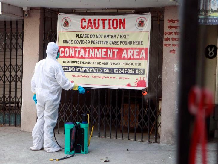 मुंबई के एक कंटेनमेंट जोन में कीटनाशक का छिड़काव करने पहुंचा बीएमसी कर्मचारी।