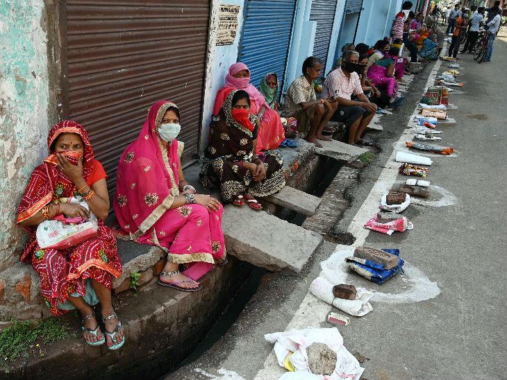 प्रयागराज में ये मजदूर सरकारी राशन लेने आए हैं। धूप तेज थी, इसलिए इन्होंने सड़क पर सोशल डिस्टेंसिंग के लिए बनाए गए गोलों में अपने झोले रखे और खुद छाया में बैठ गए।