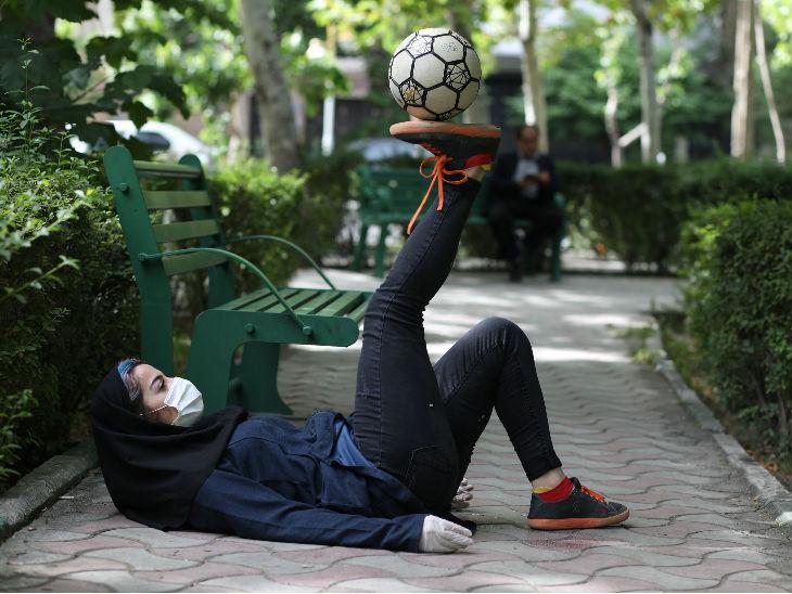 ईरान की फ्रीस्टाइल फुटबॉलर होस्ना मिरहदी मास्क और गलव्स पहनकर तेहरान के एक पार्क प्रैक्टिस करती हुई।
