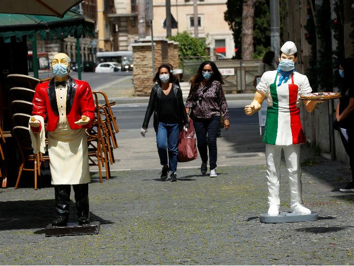 इटली में रेस्टोरेंट के बाहर वेटर के स्टैच्यू को मास्क पहनाया गया है। यहां प्रतिबंधों में कुछ ढील दी गई है। लोग रेस्टोरेंट से खाना पैक करा सकते हैं।