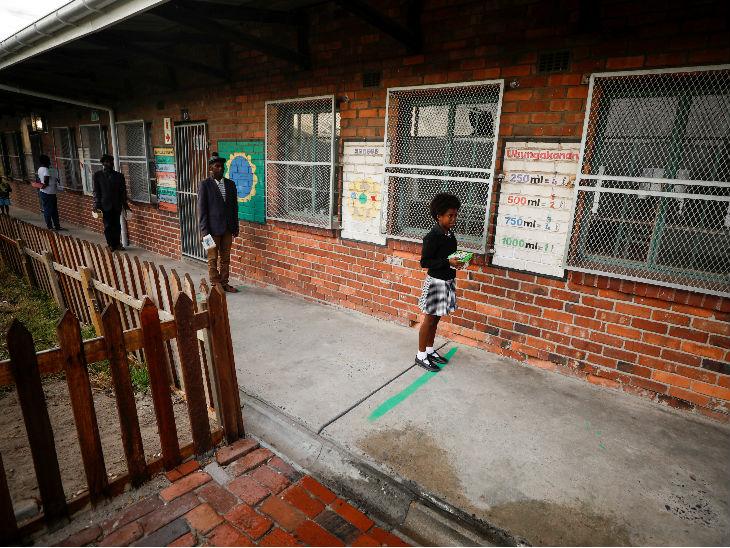 दक्षिण अफ्रीका के एक स्कूल में सोशल डिस्टेंसिंग का पालन करते हुए भोजन के लिए लाइन में लगे लोग।
