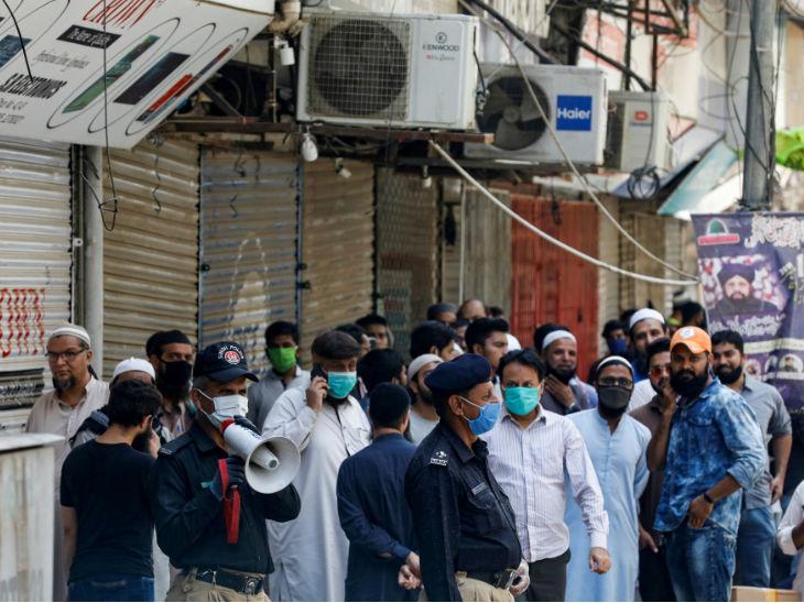 कराची के इलेक्ट्रॉनिक्स मार्केट में दुकानें बंद करने का ऐलान करता पुलिस अधिकारी। सरकार 9 मई से यहां बंदिशें कम कर सकती है।