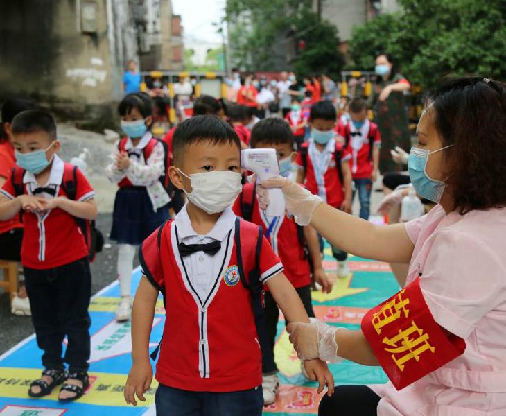 चीन के योंगझाऊ के एक स्कूल में मंगलवार को बच्चों का टेम्परेचर चेक करती टीचर। देश के कई हिस्सों में स्कूल खुल गए हैं। राजधानी बीजिंग में स्कूल और कॉलेज 1 जून से खुलेंगे।