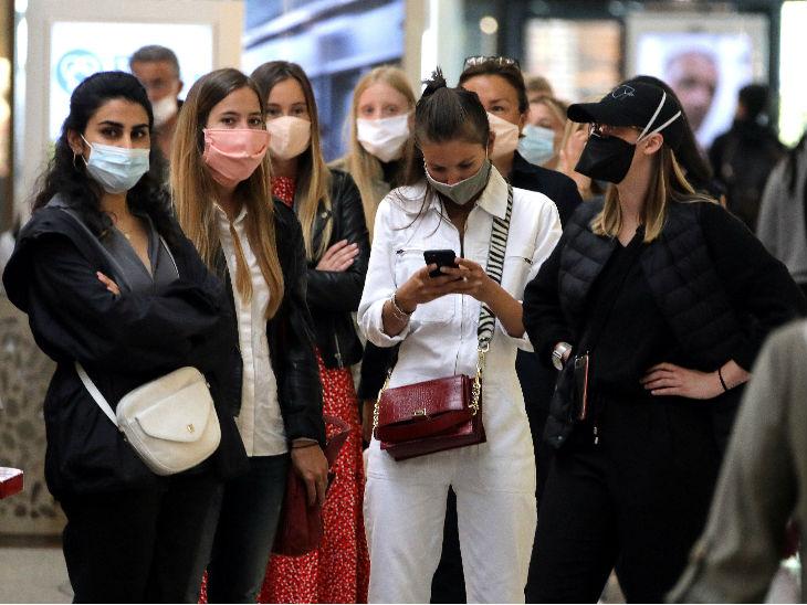 फ्रांस में एक डिपार्टमेंटल स्टोर में जाने के लिए इंतजार करती महिलाएं। सरकार ने यहां प्रतिबंधों में थोड़ी ढील दी है।