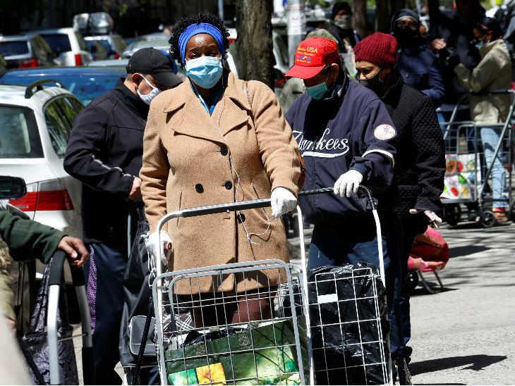 न्यूयॉर्क के मैनहट्टन में फ्री फूड के लिए लाइन में अपनी बारी का इंतजार करते लोग। राज्य में 27 हजार से ज्यादा मौतें हो चुकी हैं।
