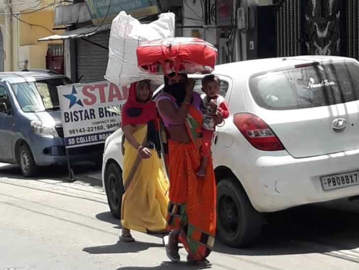 यह तस्वीर जालंधर की है। पंजाब से हजारों की संख्या में मजदूर घर के लिए पैदल ही निकल पड़े हैं। तपती धूप से बचने के लिए इस महिला ने कंबल का बैग अपने सिर पर रख लिया और बच्चे को गोद में ले लिया।