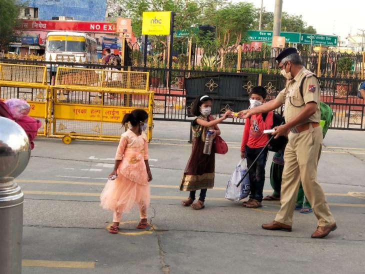 बच्चों को स्टेशन पहुंचने पर बिस्कुट देते एक पुलिस अधिकारी।