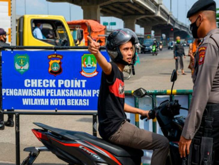इंडोनेशिया के जकार्ता में लॉकडाउन के बावजूद बाहर निकलने पर पूछताछ करते पुलिसकर्मी।