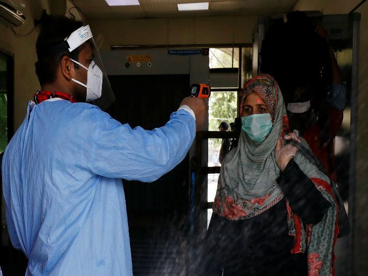 पाकिस्तान के कराची रेलवे स्टेशन पर शुक्रवार को एक महिला का टेम्परेचर चेक करता हेल्थ वर्कर।