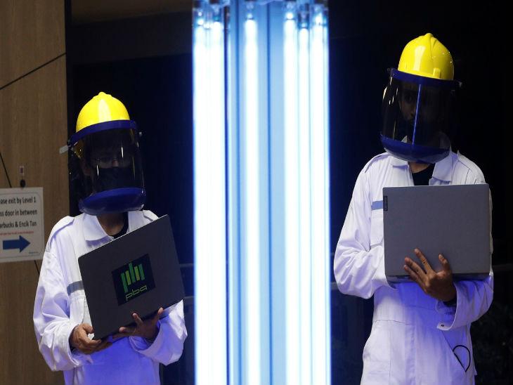 सिंगापुर के एक मॉल में अल्ट्रावॉयलेट किरणों से वायरस डिसइनफेक्ट करने वाला रोबोट को कंट्रोल करते कर्मचारी।