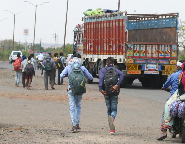 भोपाल में हाईवे पर ट्रक चालक से आगे तक ले जाने की गुहार करते प्रवासी।
