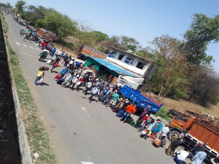 बस में सवार होने के लिए तपती दोपहरी में लाइन में लगने को मजबूर हैं मजदूर।