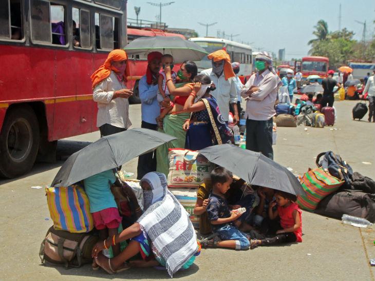 तस्वीर मुंबई के दहिसर नाका की है। ये प्रवासी अपने गांव-शहर जाने के लिए बस का इंतजार कर रहे हैं। धूप से बचने के लिए एक छाते के नीचे 4 से 5 लोग बैठे हैं।