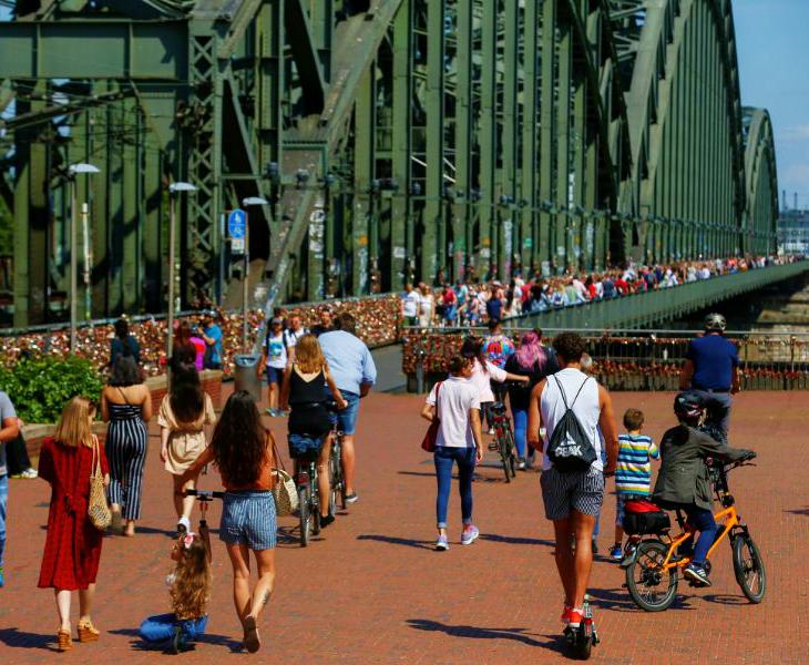 जर्मनी के कोलोन शहर में रविवार को एक ब्रिज से गुजरते लोग। यहां एक ही जगह से 107 लोगों के संक्रमण का मामला सामने आया है। हेल्थ डिपार्टमेंट इसकी जांच कर रहा है।