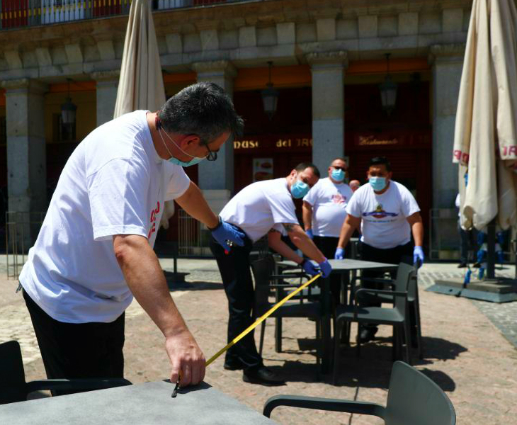 स्पेन के मैड्रिड में एक रेस्टोरेंट शुरू करने से पहले टेबलों के बीच 6 फीट दूरी मापते कर्मचारी। सरकार के मुताबिक, स्पेन में हालात पहले से काफी बेहतर हुए हैं लेकिन अब भी ऐहतियात रखने की सख्त जरूरत है।
