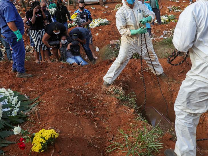 ब्राजील के एक कब्रिस्तान में कोरोना से जान गंवाने वाले एक युवक के शव को दफन करते परिजन।