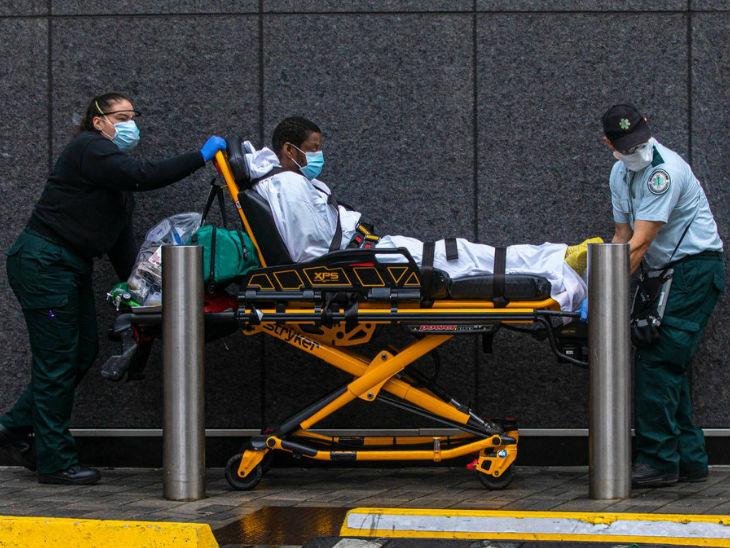 कैलिफोर्निया में कोरोना मरीज को अस्पताल ले जाते स्वास्थ्यकर्मी।
