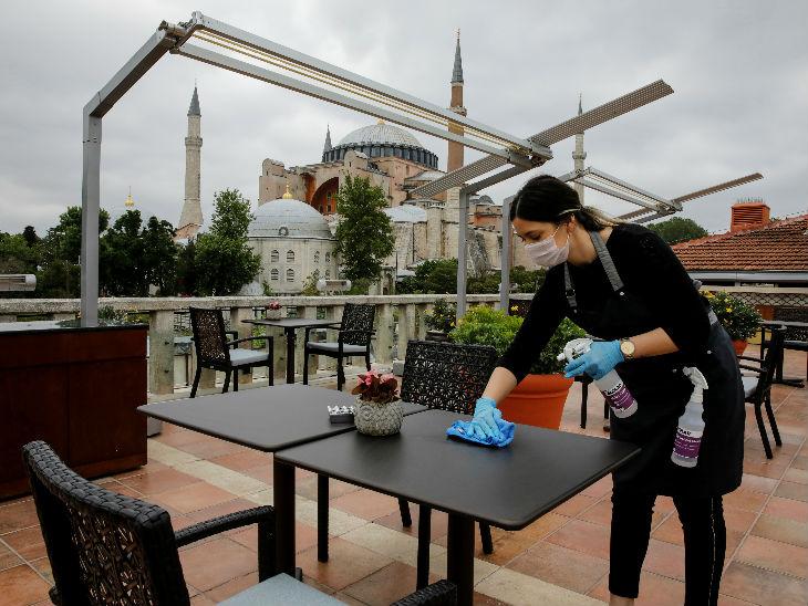 इस्तानबुल में एक होटल स्टाफर टेबल साफ करती हुई। एशिया में तुर्की में सबसे ज्यादा मामले हैं।
