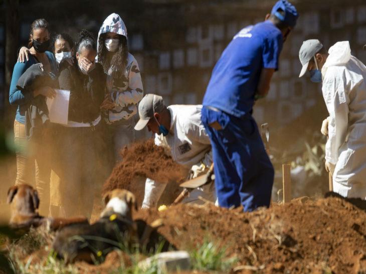 ब्राजील के साओ पाउलो स्थित एक कब्रिस्तान में कब्र खोदते कर्मचारी।