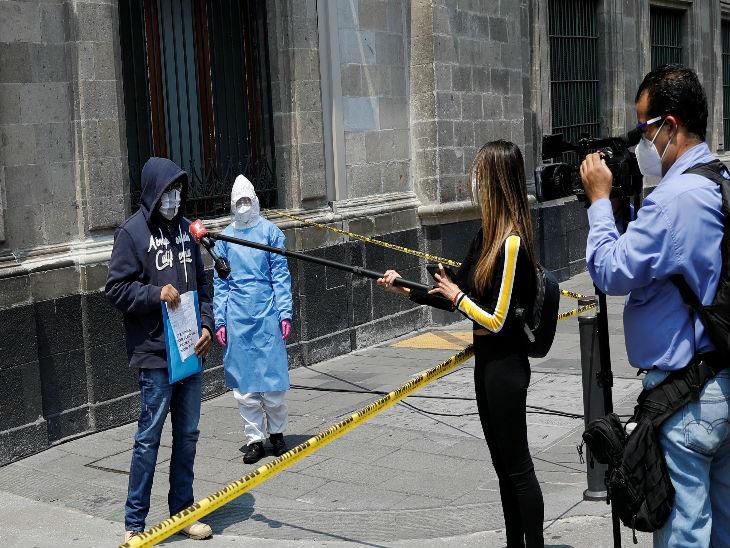 न्यू मैक्सिको सिटी में खुद के काेरोना संक्रमित होने का दावा करने वाले एक व्यक्ति का इंटरव्यू लेते पत्रकार।