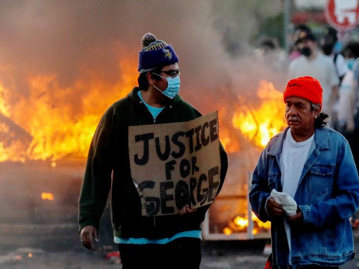अमेरिका के मिनेपोलिस में अफ्रीकन-अमेरिकी व्यक्ति जॉर्ज फ्लॉड की मौत के विरोध में प्रदर्शन करता एक व्यक्ति।