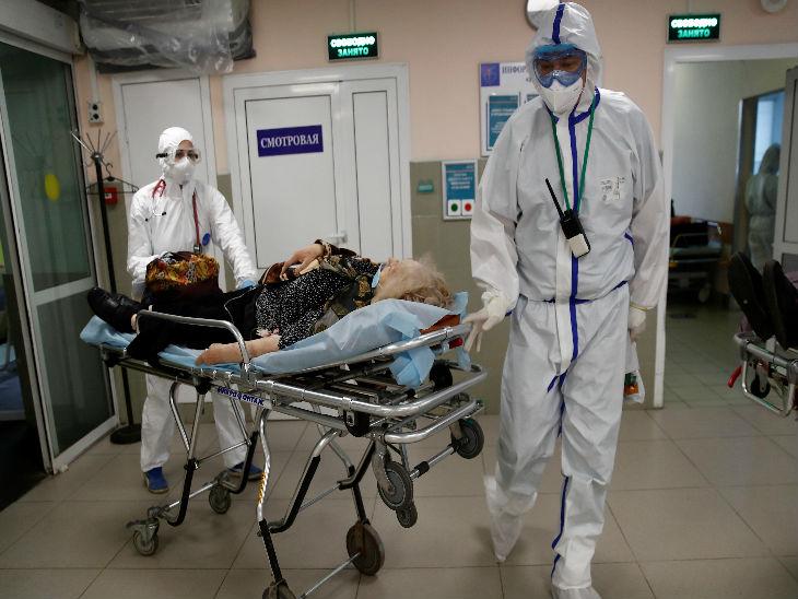 रूस की राजधानी मॉस्को के एक अस्पताल में बुधवार को स्ट्रेचर पर मरीज को ले जाते स्वास्थ्यकर्मी।