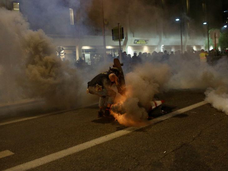 एरिजोना में पुलिस द्वारा फेंके गए आंसू गैस के गोले से बचने का प्रयास करता प्रदर्शनकारी।