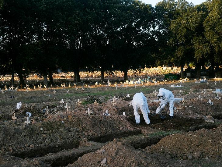 रियो डी जेनेरियो में स्थित एक कब्रिस्तान में कोरोना से जान गंवाने वाले युवक का शव दफन करते लोग।