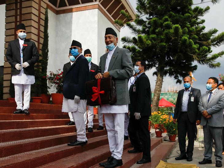 मास्क पहने नेपाल के वित्त मंत्री युबा राज खातिवाडा 2020-21 के बजट के साथ संसद में जाते हुए।