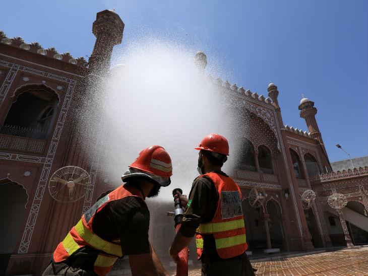 पाकिस्तान के पेशावर शहर में एक मस्जिद को सैनिटाइज करते सरकारी कर्मचारी।