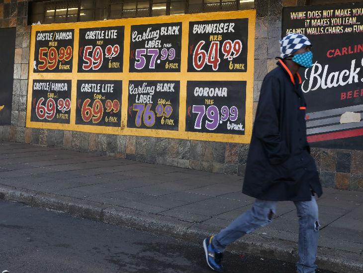 दक्षिण अफ्रीका में एक बंद वाइन शॉप के पास से मास्क पहनकर गुजरता युवक।