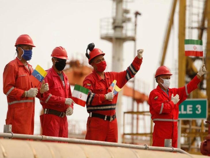 वेप्युर्टो कैबेलो बंदरगार पर ईरान से तेल टैंकर पहुंचने के बाद स्वागत में झंडा लहराते वेनेजुएला की सरकारी तेल कंपनी के कर्मचारी।
