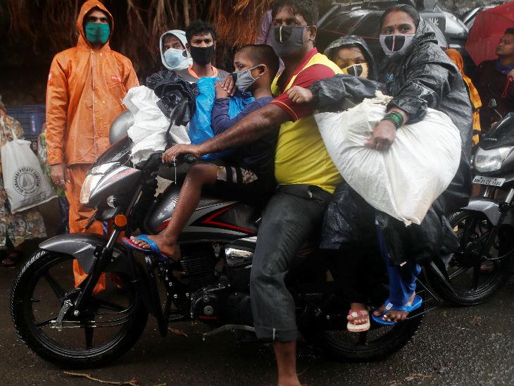 मुंबई की एक झुग्गी बस्ती से एक व्यक्ति अपने परिवार और सामान के साथ बाइक से जाता हुआ। तूफान से पहले यहां से लोगों को सुरक्षित स्थानों पर भेजा गया।