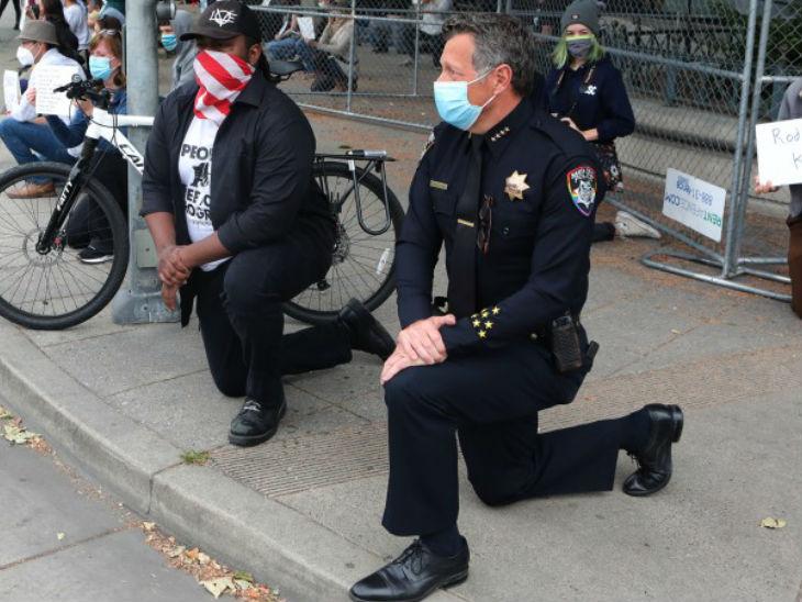 सांता क्रूज के मेयर जस्टिन कमिंग्स (बाएं) और पुलिस चीफ एंड्रयू मिल्स प्रदर्शन कारियों के सामने अपना समर्थन जताने के लिए घुटनों पर बैठ गए।