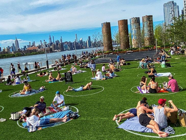 न्यूयॉर्क में सोशल डिस्टेंसिंग के नियम का पालन करते हुए डोमिनो पार्क में बैठे लोग।