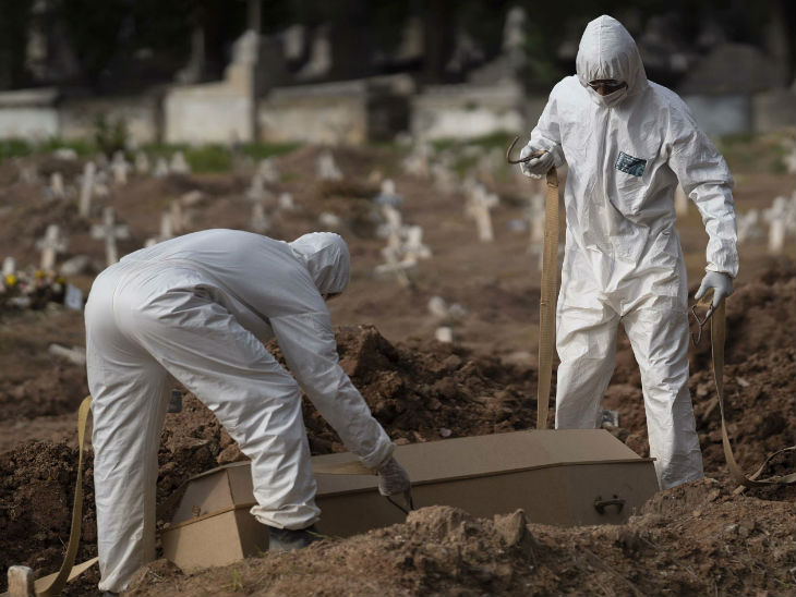ब्राजील के रियो डि जेनेरो में कोरोनावायरस से मौत के बाद 57 साल के पाउलो जोस का शव दफनाते कब्रिस्तान के कर्मचारी। पाउलो जोस की सौतेली बेटी मोनीक ने बताया कि पाउलो बहुत से ब्राजीली लोगों की तरह मास्क नहीं पहनते थे और किसी गाइडलाइन का पालन नहीं करते थे।